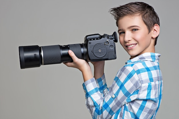 少年は望遠レンズ付きの大きな写真カメラを持っています