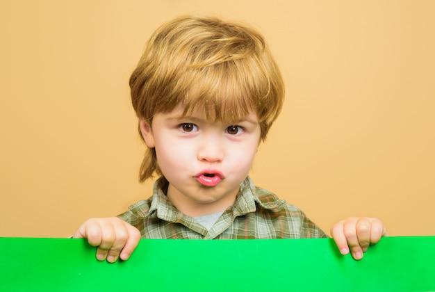 Мальчик держит пустую доску ребенок мальчик держит пустой рекламный щит маленький мальчик держит пустой рекламный баннер