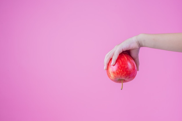 Boy holds and eats red apples on a pink background.