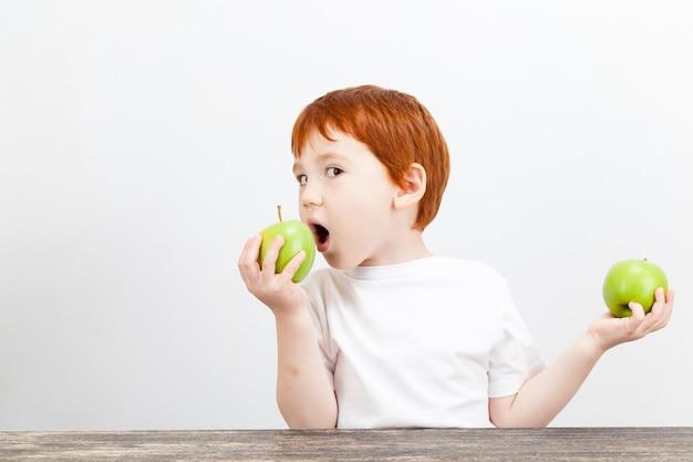 소년은 녹색 사과를 손에 들고 밝은 배경에 두 번째 사과를 먹는다.