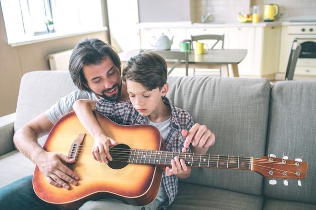 Мальчик держит гитару и пытается играть