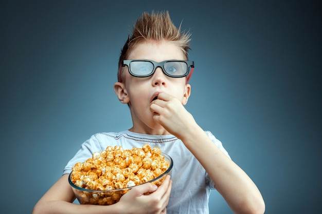 The boy holds in his hands and eats popcorn watching a movie in 3d glasses, blue wall. the concept of a cinema, films, emotions, surprise, leisure. streaming platforms.