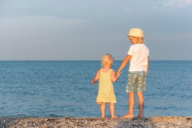 少年は海岸で小さな女の子を手で持っています。のんきな子供時代。