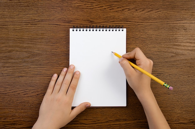 Boy holds pencil in hand and writes into notebook