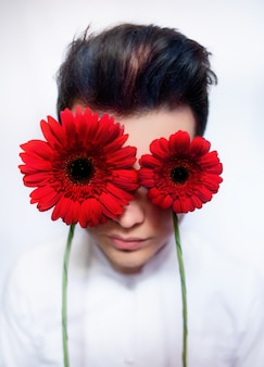 Boy holds red flowers before his eyes