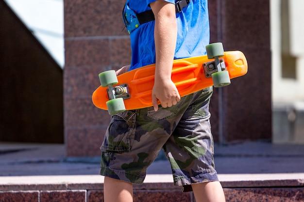少年は彼の手でスケートを保持します