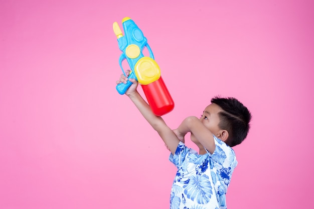 The boy holds a water gun on a pink background.