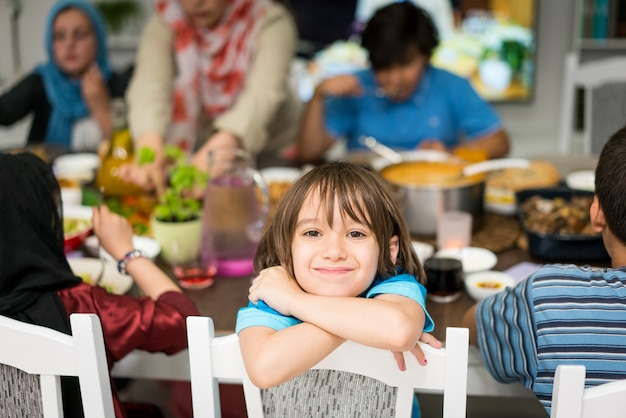 A boy at home having lunch with his family and friends