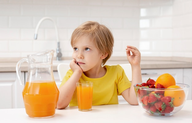 Boy at home in kitchen eating fruits