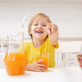 Boy at home in kitchen pointing