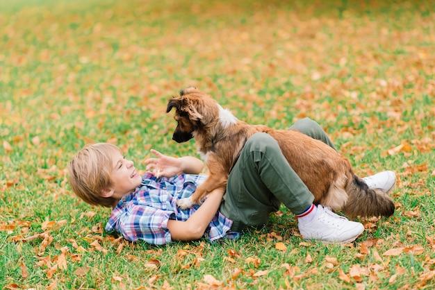 Мальчик обнимает собаку и играет осенью в городском парке