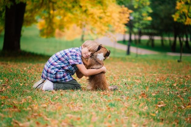 犬を抱き締めて秋に遊ぶ少年、都市公園