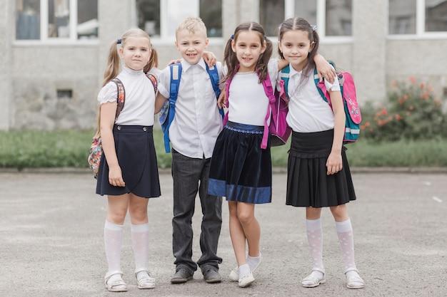 Мальчик обнимает девочек возле школы