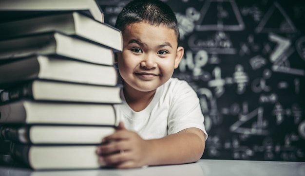 A boy hugging a pile of books.