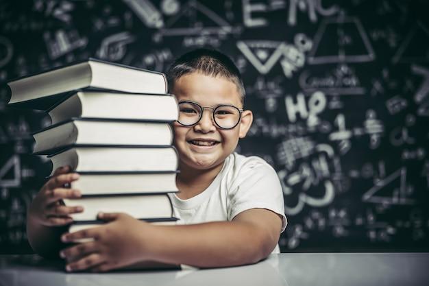 Un ragazzo che abbraccia una pila di libri.