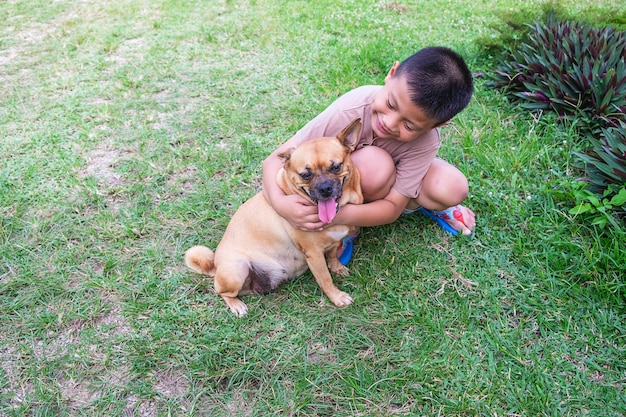 The boy hugs his dog happily.