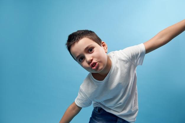 少年は翼のように腕を広げて飛行を模倣します