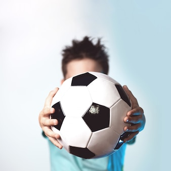 Мальчик в синей футболке держит футбольный мяч в руках, закрывая голову