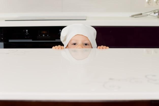 그의 눈만 보이는 부엌에서 카운터 너머로 들여다 보며 요리사 모자에있는 소년