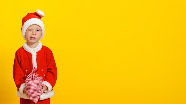 Мальчик в костюме рождественского деда мороза держит красную в белой клетке сумку и лукаво улыбается