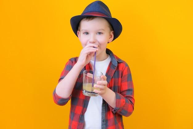 모자를 쓴 소년은 빨대로 주스를 마신다. 편안한 개념입니다. 노란색 배경