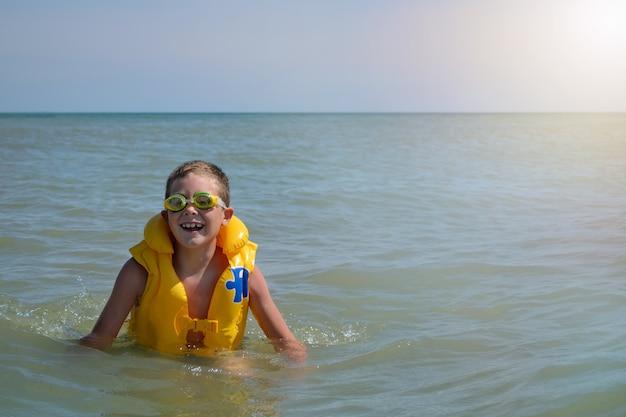 水中で救命胴衣を着た少年。うれしそうな子供は晴れた日に海で夏休みを過ごします。バナー
