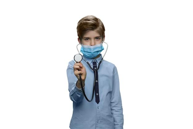 청진기를 사용하여 심장이나 폐를 듣고 의료 마스크 소년