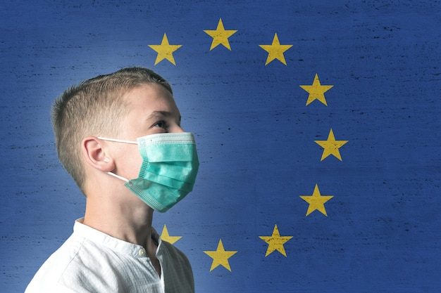 欧州連合の旗を背景に彼の顔に医療マスクの少年。