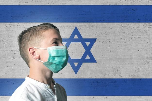 イスラエルの旗の背景に彼の顔に医療マスクの少年。