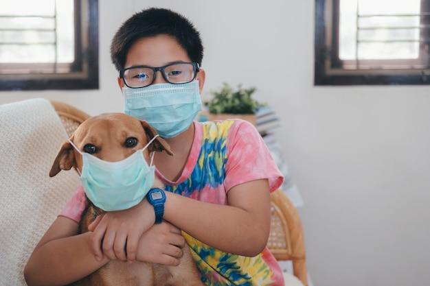 医療マスクの少年は彼の犬に医療マスクを置きます。