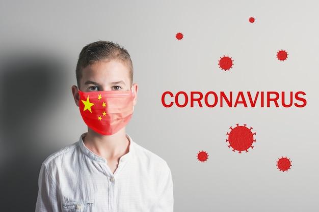 明るい背景に彼の顔に中国の旗と医療マスクの少年。