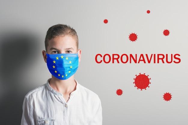 明るい背景に彼の顔に欧州連合の旗と医療マスクの少年。