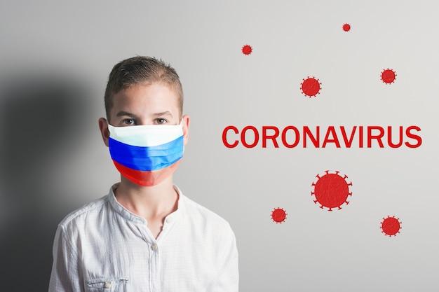 明るい背景に彼の顔にロシアの旗と医療マスクの少年。