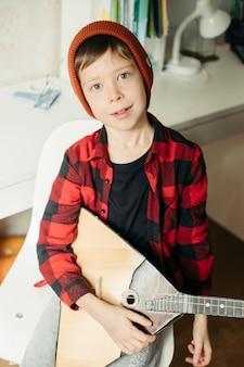 赤い帽子と格子縞のシャツを着た少年がバラライカを演じます。彼のギターを持っているハンサムな男の子。自宅での音楽レッスン。魂の趣味。ホームティーチングミュージック