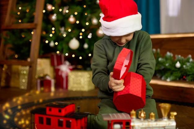 赤い帽子をかぶった少年が魔法のクリスマスツリーから贈り物を取り出します