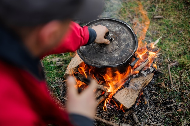 たき火の上に立っている黒い鍋にカバーを置き、赤いジャケットと暗い帽子をかぶった少年