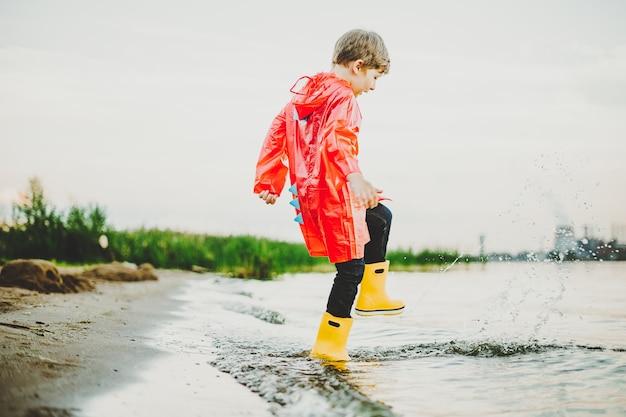 Мальчик в красном плаще и желтых резиновых сапогах играет с водой у школьника на пляже в