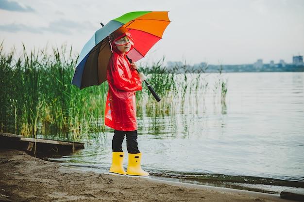 Мальчик в красном плаще и желтых резиновых сапогах стоит на берегу реки и держит радужный зонтик