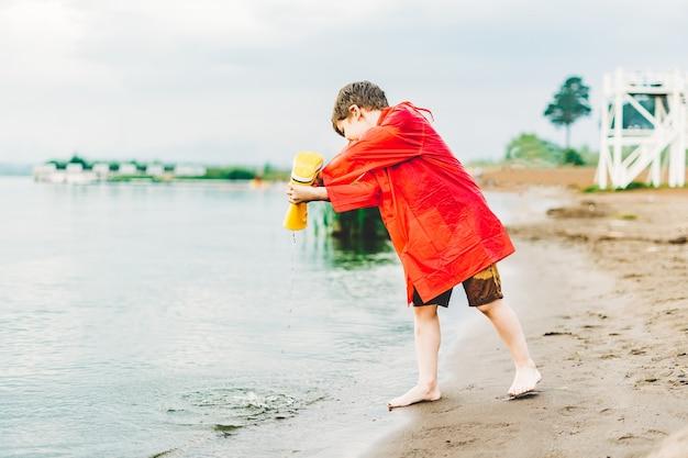 Мальчик в красном плаще льет воду из желтого резинового сапога в озеро. ребенок играет с водой.