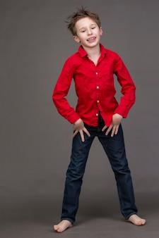 회색 배경에 빨간 셔츠와 청바지를 입은 소년 모델링 사업에 있는 아이가 포즈를 취하고 있다