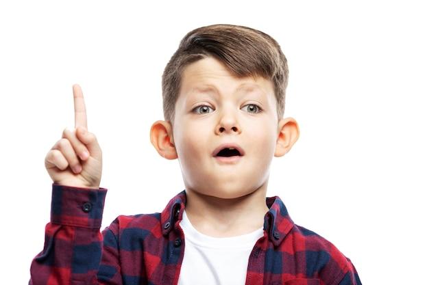 赤いシャツを着た少年が人差し指を上げて、アイデアを持っています