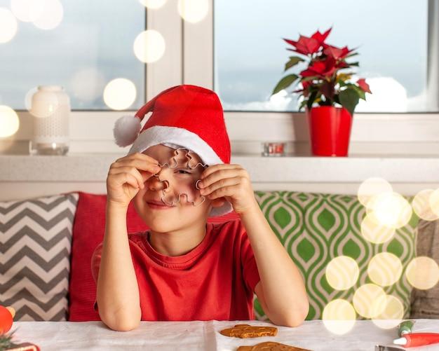 サンタクロースの帽子をかぶった少年は、新年のジンジャーブレッドクリスを調理するクッキーカッターを通してふざけて見えます...