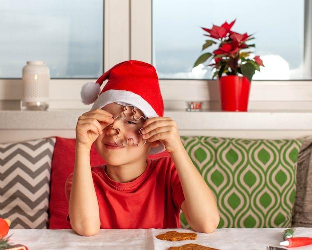 サンタクロースの帽子をかぶった少年は、新年のジンジャーブレッドを調理するクッキーカッターを通してふざけて見えます