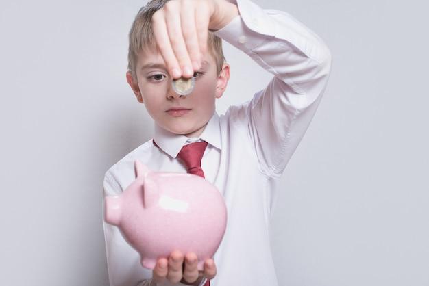 셔츠와 넥타이를 입은 소년은 분홍색 돼지 저금통에 동전을 넣습니다. 비즈니스 개념.