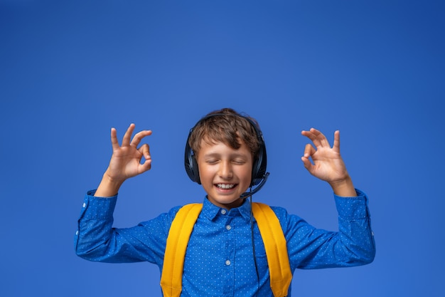 ヘッドフォンとバックパックのシャツを着た少年