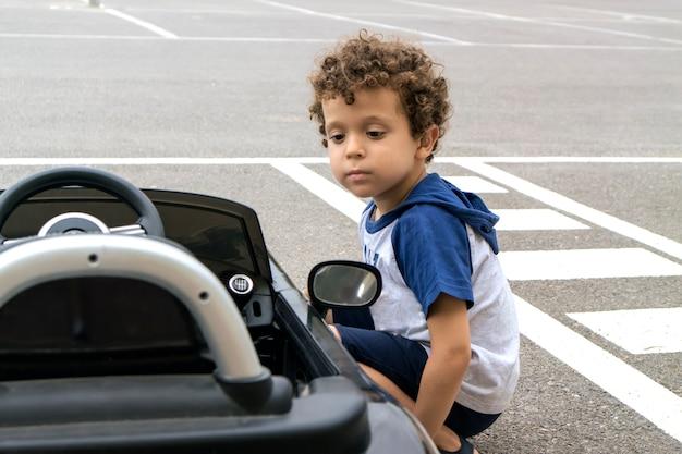 彼の黒いコンバーチブル電気自動車の隣にしゃがんだ位置にいる少年