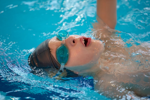 수영장에서 수영 모자와 수영 고글을 쓴 소년