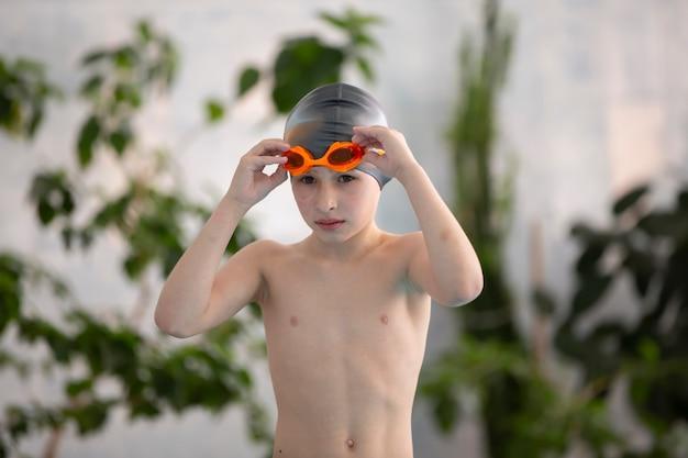 스포츠 수영장에서 수영 모자를 쓴 소년.