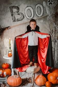 Мальчик в костюме вампира дракулы на хэллоуин стоит среди тыкв