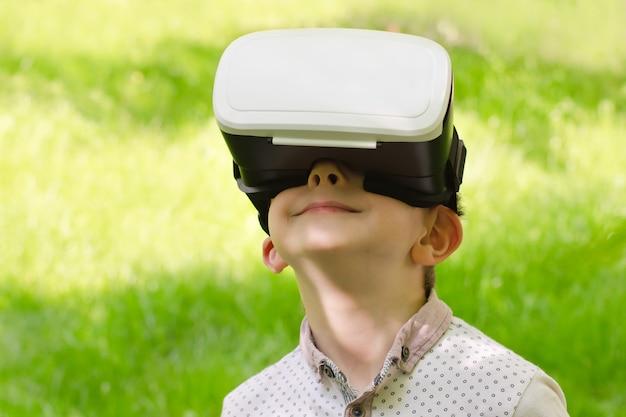 Мальчик в шлеме виртуальной реальности на фоне зеленой травы